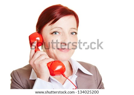 Happy elderly business woman with red phone receiver - stock photo