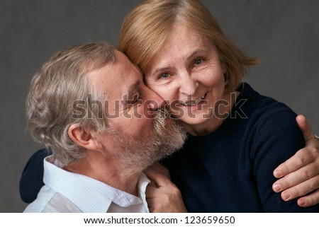Happy elderly couple/An elderly man hugs and kisses his wife. Studio photography, close-up - stock photo