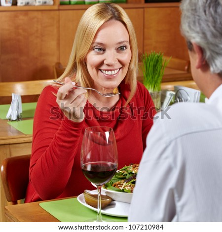 Happy elderly couple eating dinner together in a restaurant