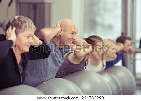 Happy elderly couple exercising in a pilates class at the gym with three other younger people toning and strengthening their muscles using gym balls, focus to the senior man and woman - stock photo