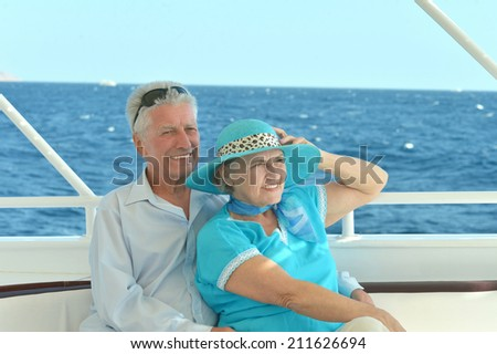 Happy elderly couple have a ride in a boat on sea