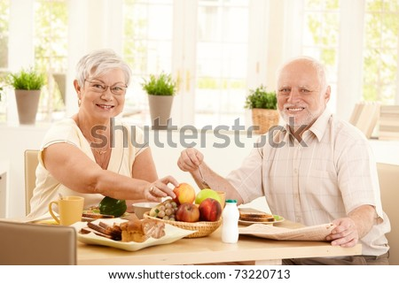 Happy elderly couple having breakfast in kitchen, smiling at camera.? - stock photo