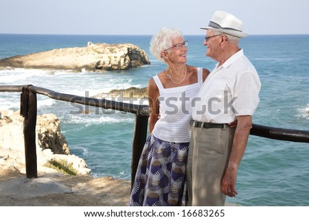 happy elderly couple having fun outdoors, looking in each other's eyes - stock photo