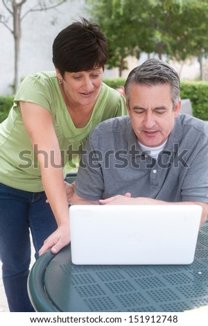 Happy elderly couple in a park doing work - stock photo