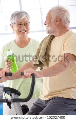 Happy elderly couple in the gym, man on fitness cycle. - stock photo