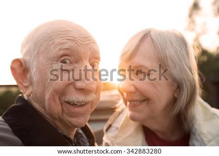 Happy elderly couple joking together outdoors at sunset - stock photo