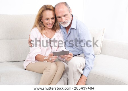 Happy elderly couple looking at a tablet