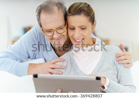 happy elderly couple looking at a tablet as they are surfing the internet