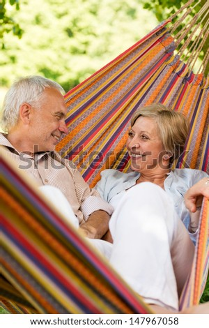 Happy elderly couple lying in hammock