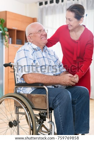 Happy elderly couple of   woman and   man  in   wheelchair