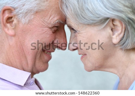 happy elderly couple on a gray background - stock photo