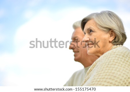 Happy elderly couple posing against the sky - stock photo