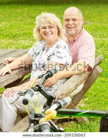 Happy elderly couple relaxing in the park after ride bike.