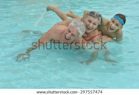Happy Elderly couple resting at pool water together with grandson - stock photo