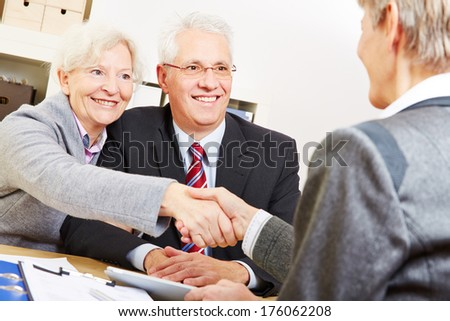Happy elderly couple shaking hands with legal consultant in law firm - stock photo