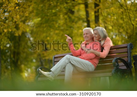 Happy elderly couple sitting on bench in autumn park - stock photo