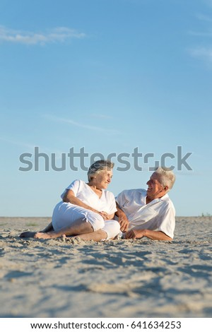 Happy elderly couple sitting on the sand