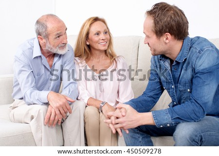 happy elderly couple talking with a younger man