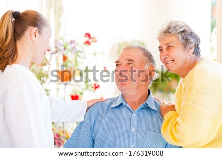 Happy elderly couple talking with their carer - stock photo