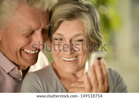 Happy elderly couple with a mobile phone - stock photo