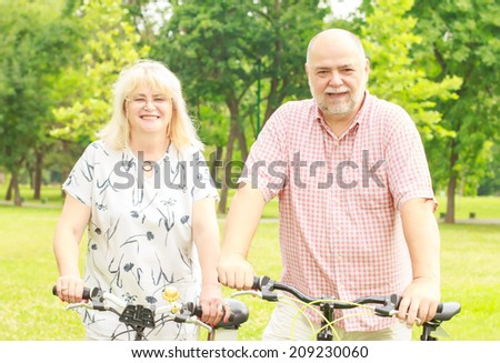 Happy elderly couple with bike in the park.
