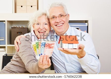 Happy elderly couple with fan of Euro money and little house in their hands - stock photo