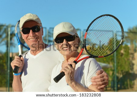 Happy elderly couple with tennis racket in hand - stock photo