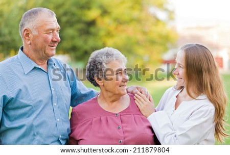Happy elderly couple with their carer in the nature - stock photo
