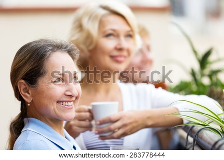 Happy elderly female colleagues having lunch break at patio and drinking tea - stock photo