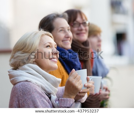 Happy elderly female friends drinking coffee at patio. Focus on blonde
