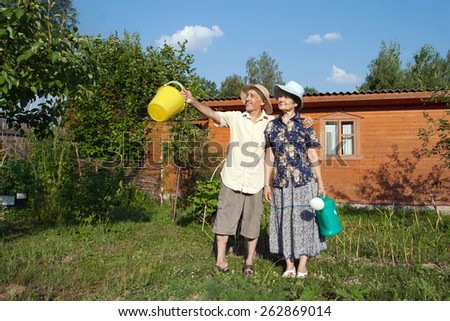 Happy elderly gardeners with a pail and watering can - stock photo