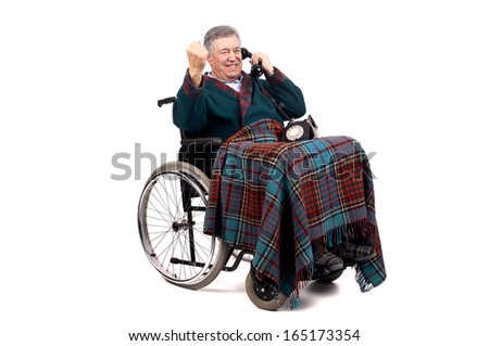 Happy elderly in a wheelchair receiving a call from his family - stock photo