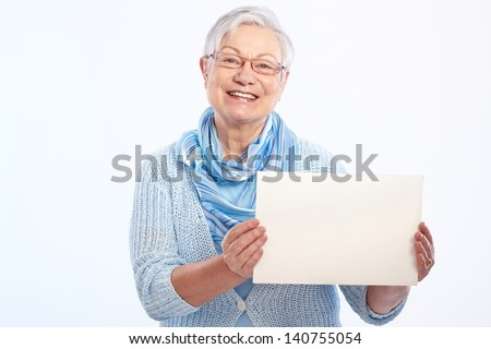 Happy elderly lady holding blank sheet in hand, smiling. - stock photo