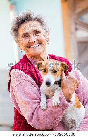 Happy elderly lady holding her little pet dog outdoors in the garden.