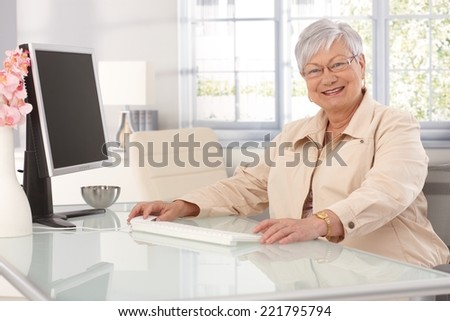 Happy elderly lady sitting at table at home, using computer, smiling at camera. - stock photo