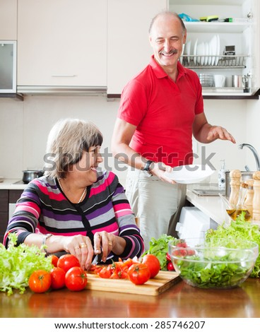 happy elderly man and mature woman  doing chores together in the kitchen