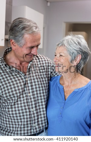 Happy elderly man and woman standing in the kitchen - stock photo
