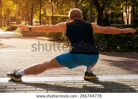 Happy elderly man doing exercises on urban district sports ground - stock photo