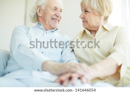 Happy elderly man looking at his wife - stock photo