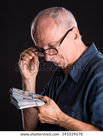Happy elderly man showing dollars on a dark background