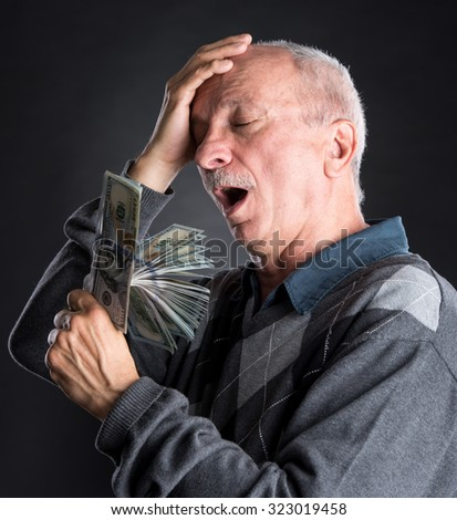 Happy elderly man showing dollars  on a dark background with copy-space - stock photo