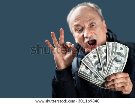 Happy elderly man showing fan of money and sign OK with fingers on blue background with copy-space. Focus on money and hand with blurred face.