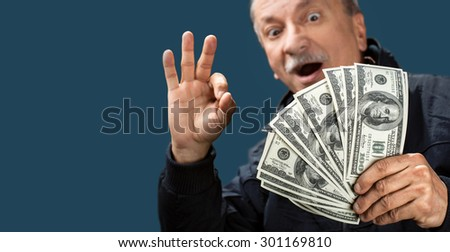 Happy elderly man showing fan of money on blue background with copy-space. Focus on money. Softly blurred face - stock photo