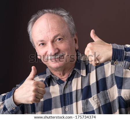 Happy elderly man showing ok sign on a brown background