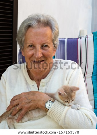 Happy,elderly, senior woman with rescue pet kitten - stock photo
