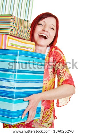 Happy elderly woman carrying many christmas gifts - stock photo