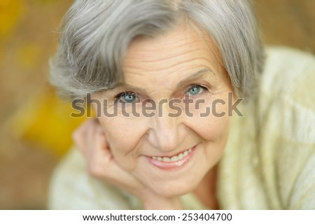 Happy elderly woman enjoying in autumn park - stock photo