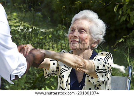 Happy elderly  woman in wheelchair welcoming visitor - stock photo