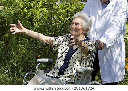 Happy elderly  woman in wheelchair with open arms, welcoming - stock photo
