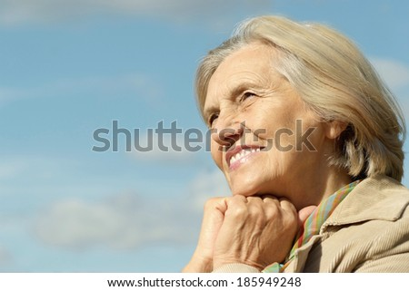 Happy elderly woman posing against the sky - stock photo